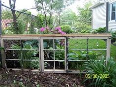 "Dianne tells about this window project. ""Then I needed a visual divider between my vegetable garden and collection of hostas so I took 3 windows (also removed the glass). I positioned them on their sides, hung beads and crystals in the center of each pane and attached them on the top and bottom with 2x4 for stability. They serve as a low wall"""