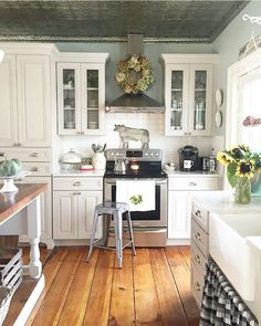 White kitchen cabinets with rich hardwood flooring.