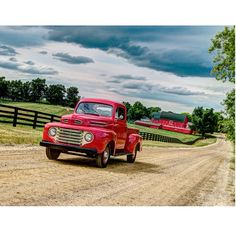 Vintage cherry red truck driving down a country dirt road. Red barn. Wood fence. Green field.