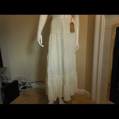 """Billabong Tiered Peasant Maxi Skirt, Off-White New with tags Billabong tiered peasant skirt.  The color is off-white/cream.  Size Small.  Elastic waistband, four tiers of fabric, rolled hem.  Style #JK05TLON, Cut #T4107.  60% cotton, 40% viscose.  Machine wash cold.  Made in India.  Measurements: Length:  39"""" Waist:  23"""" Hips:  32""""  NOTE: Mannequin shown has the following measurements – 40"""" (shoulders), 34"""" (bust), 24"""" (waist), 34"""" (hips), 68"""" (height). Billabong Skirts Maxi"""