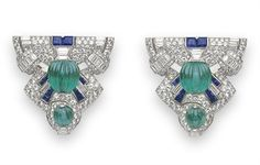 AIR OF ART DECO DRESS CLIPS, BY RAYMOND YARD – Christie's Each designed as a tapered openwork circular and baguette-cut diamond geometric plaque, set with two carved emerald beads, accented by calibré-cut sapphires, mounted in platinum, circa 1925
