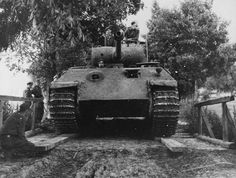 """German tank Pz.Kpfw.V «Panther"""" from the 5th SS Division Viking is getting ready to pass on the wooden bridge over the river."""
