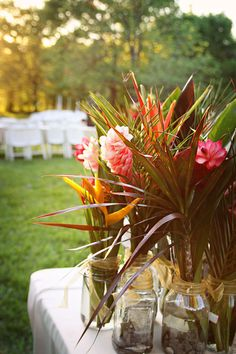 Tropical flowers for bar and buffet tables - maybe I can get the flowers at wholefoods and just stick them in jars/vases.