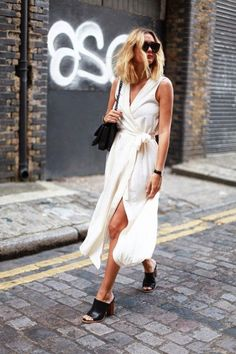 A white sleeveless wrap dress is worn with black stacked mules, black shoulder bag and sunglasses #streetstyle #fashion