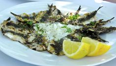 Grilled Greek sardines accompanied with onions and lemon