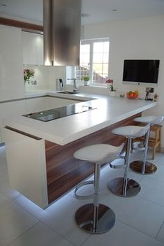 White matt lacquered kitchen with wood grain looking panel. Nice peninsula seating area: Kitchen bar