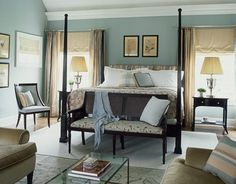 """Zoffany's Broccatello Ciniglia—the fabric on the bench—inspired the master bedroom palette. Walls are painted Powder Blue #23 by Farrow & Ball. Putting a light-colored carpet on dark floors """"makes the bed feel like it's floating,"""" Sanders says. The small needlepoint rug defines the sitting area. The David Iatesta Loire four-poster bed and Manheim-Ruseau Townsend Dining Chair are through John Rosselli. Print blanket and bed linens from Frette."""