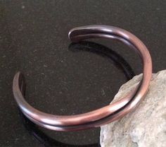 This is a handmade pure copper bracelet that is a lighter version of my heavier design. It is forged out of new 6 gauge pure copper wire and is approximately 5/16 inch (7.94 mm) wide. I annealed a single piece of wire, hammered the center and ends uniformly then formed it into the desired size bracelet. After shaping for a perfect fit, it was tumbled in a jewelers mix to remove the rough edges and polish for a smooth comfortable wear. Finally, it was oxidized to achieve a really nice pat...