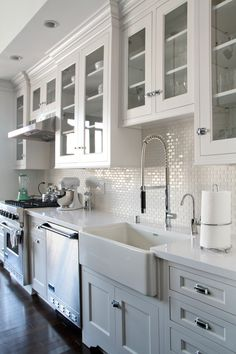 white kitchen cabinets, glass doors, dark wood floors. Backsplash - white mini subway tile