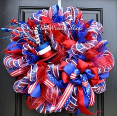 Bright Patriotic Wreath on Red White and Blue Striped Deco Mesh with patriotic ribbons, large bow, and glittery whimsical hat. Measures 26 inches.