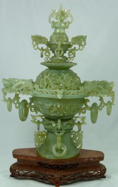 """A Chinese reticulated celadon jade lidded dragons censor. Intricately carved throughout to depict numerous dragons to screen, handles and base. Has hight relief dragons to body. Late Qing dynasty period. Includes fitted wooden base. Measures 14 1/2"""" height x 11 1/2"""" width + 2 1/2"""" base height (36.8cm x 29.2cm + 6.3cm). Total jade weight of 2443 grams."""