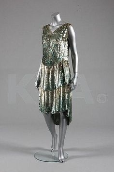 A 'cobweb' sequined flapper dress, French, circa 1928, the pale green muslin ground adorned in delicate shades of green-silver sequins, with scalloped, graduated hem