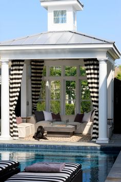 .small pool house, horizontal black and white striped curtains.