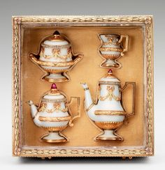 Miniature tea service,Creator: Fabergé  Comprising a teapot, hot water pot, sugar bowl and milk jug, this tea set is of gold enamelled in a pale opaque bluish-white, but there is no engine turning on the metal. This deliberately plain enamelling creates the impression that the tea set is made of porcelain. The lids are each surmounted by a finial in the form of a cabochon ruby