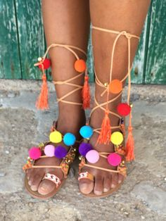 Made with much love , our super trendy Ibiza style tie up gladiator sandals are decorated with colourful pom poms , charms and hand made braided ethnically friendship lace borders , makes it the most wanted bohemian summer sandal for the summer Each pair is a unique hand made creation , you will love it .    Hand made decorated with extra beads , charms and hippy tassels Hand Braided colourful friendship bands Gripped rubber sole for extra comfort strap tie up to embrace the legs with extra…
