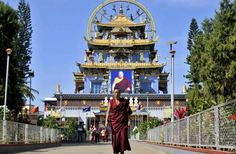 A Tibetan Buddhist monk walks in front of the Golden Temple inside the Nyingmapa Monastery in...