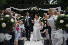 Bride and groom coming down the aisle after their outdoor ceremony at Swynford Manor in Cambridgeshire