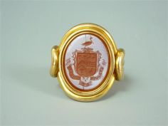 An antique signet ring, the oval carnelian matrix bearing an intaglio armorial, set on a heavy high carat precious yellow metal fancy shank, 13.3g total weight