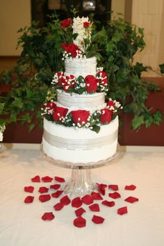 """""""Red Rose Towel Cake"""" shown on display on the gift table at a wedding reception"""