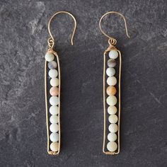 Golden wire surrounds a pathway of delicate gems or pearls to form these graceful drop earrings, each pair hand-crafted by Houston designer Hila. Pairing quality workmanship with an artist's eye for design, Hila Graham finds inspiration in the ebb and flow of nature, and looks beyond the purpose of functional items to find beauty in the everyday.