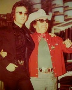 """John Lennon and Nudie Cohn (Nuta Kotlyarenko, known professionally as Nudie Cohn (December 15, 1902 – May 9, 1984), was a Ukraine-born American tailor who designed decorative rhinestone-covered suits, known popularly as """"Nudie Suits"""", and other elaborate outfits for some of the most famous celebrities of his era. He also became famous for his outrageous customized automobiles.)"""