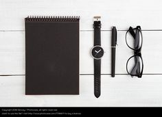 Notepad, watches, pen and glasses on the desk
