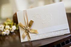Convite de casamento com monograma em relevo seco e fita de cetim dourada.