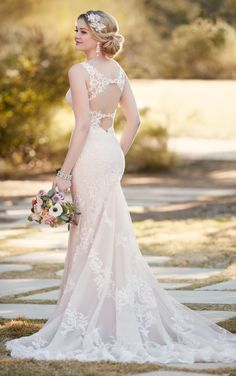 Romantic lace swirls throughout this elegant sheath wedding dress from Essense of Australia. Featuring elegant tulle over Imperial crepe, the bodice is lightly fitted and the back features an exquisite double keyhole back. Crystal buttons hide it's easy-close zipper.
