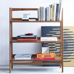 Library building. Inspired by American modern design, the Mid-Century Low Bookshelf borrows its slim legs and bevelled edges from iconic '50s and '60s furniture silhouettes. Consisting of a three wide, fixed shelves, it makes for practical extra storage in the bedroom, study or living room.