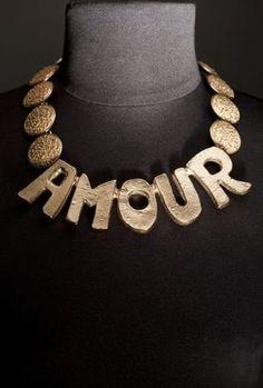 """* Yves Saint Laurent, haute couture, par Robert Goossens, circa 1980. photo courtesy Cornette de Saint Cyr Tour de cou en métal doré à motif abécédaire figurant le mot """"""""Amour"""""""" rehaussé de plaques circulaires gravées à l'imitation pépites"""