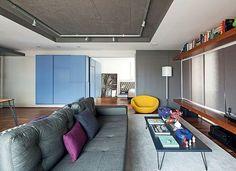 O morador Bruno Poppa queria integrar todos os ambientes do apartamento. Entre a suíte e a sala, os arquitetos do Superlimão Studio encontraram um pilar e, para disfarçá-lo, instalaram painéis de madeira. Se Bruno quiser preservar sua intimidade, é só fechar o quarto puxando-os para a lateral. Eles se escondem entre os armários azuis.