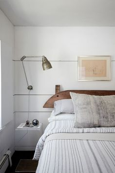 The 1700s Dutch headboard is from Red Chair in Hudson and the bedside lamp was found at Brimfield. The pillow is a custom design made with vintage fabric; for something similar, see Diani Living's Vintage Gray Batik Pillow.