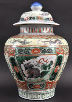 A CHINESE QING DYNASTY WUCAI PORCELAIN GINGER JAR AND COVER probably late Kangxi, painted with mythical beasts within a landscape. Minor wear. 13.5ins high.