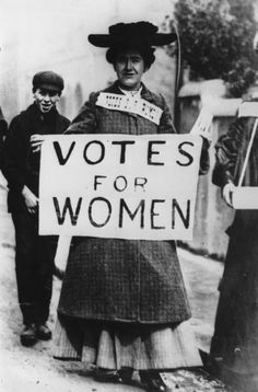 Miss Billington carries a banner enscribed with the suffragette slogan 'Votes For Women' during a demonstration at Westminster