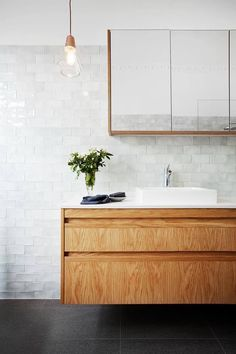 Beautiful floating wood bathroom vanity and simple tiles with organic quality and subtle texture