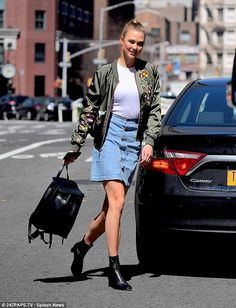 Legs for days: Leggy Karlie Kloss wears denim mini skirt and embroidered bomber jacket to check out her new fashion collection in NYC store on Monday