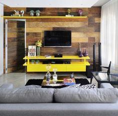 O destaque do projeto assinado pela IBD Arquitetura é o painel feito de madeira de demolição que sustenta a TV, o rack e as prateleiras. A marcenaria amarela e os objetos de arte e design dão toques contemporâneos ao ambiente rústico