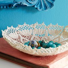 Doilies abound at flea markets and antiques stores. Pick up a few and repurpose them as storage vessels. Dip the doily into a mixture of one part crafts glue and one part water. Smooth the wet doily over an upside-down glass bowl with your hands; let dry. Carefully peel the doily away from the bowl./