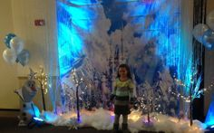 A 6 year old stands in front of her Frozen castle backdrop with lighted trees and snow.