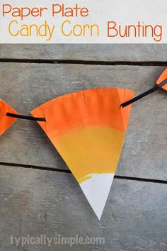 Paper Plate Candy Corn Bunting - With some paper plates, paint, and ribbon, create this festive fall candy corn bunting to hang up in the house! #halloween #can…