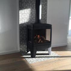 Vrijstaande kachel kan ook, maar het is mooier om de radiator weg te werken en zo een ingebouwde haard met tv meubel in een geheel te maken.