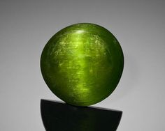 Exceptionally Rare Cat's Eye Demantoid Garnet from Kerman Province, Iran. Demantoid garnet is one of the most valuable members of the garnet family;chatoyant demantoids are almost never seen.The present circular cabochon has a vivid green color which is reminiscent of fine demantoid garnets from the Urals. With a high transparency, which at the same time displays a very strong and central cat's eye effect at the apex of its dome.Weighing approximately 7.04 carats and measuring 10.0 x 6.2 mm