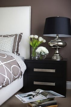 Contemporary bedroom design with aubergine walls paint color, white headboard with nailhead trim, Dwell Studio Gate Ash Duvet Set, ebony stained modern chest nightstand and silver lamp.