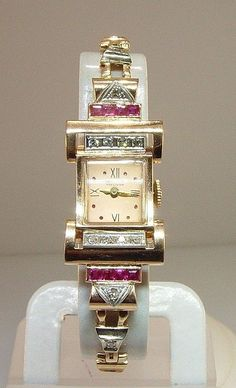 Art deco watch This manual wind-up Gruen Precision watch is one of the most unique watches we have. Estimated to be from the 1950's, it's set in 14 karat Rose Gold and features Rubies and Diamonds. The band is made of small connecting triangles, which each feature either a Diamond or a Ruby, alternating. The watch face has Roman numeral numbers for 12, 3, 6 and 9. The rest of the numbers are represented with tiny Rubies