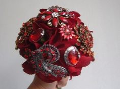 An elegant bouquet in red brooches. finished with feathers and ribbon.
