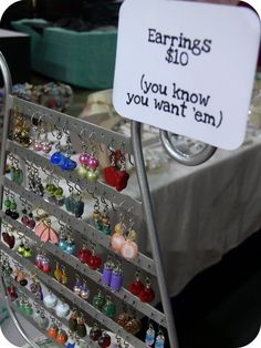 eye catching sign on the earring stand ~ I've seen metal strips with holes in them at hardware stores. Maybe they would work for a similar earring display. Nail them to a wooden frame?