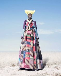 An elderly Herero woman in a patchwork dress that would be worn every day of the year; as Herero women get older, the 'horns' of their headdresses get smaller. According to some accounts, this symbolizes their loss of fertility.