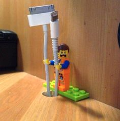 If you need a cable holder in a pinch, just use a LEGO Minifigure. | 33 Genius Life Hacks That Are Actually Useful