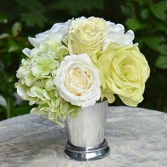 A simple and elegant designer bouquet of  white and green roses and hydrangea. Our silver metal vase is the perfect complement for this lovely design sit just aobut anywhere. Perfect  for weddings &  events.  10'' H x 8'' W x 8'' D