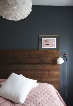 Dark and feminin bedroom with industrial bedside lamps and a rustic headboard made from old wooden planks.
